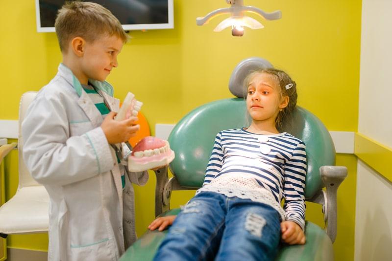little-boy-in-uniform-playing-dentist-playroom-DPKQBRS